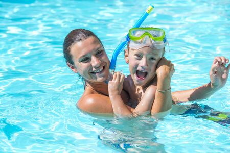 Mother playing with son in the pool.