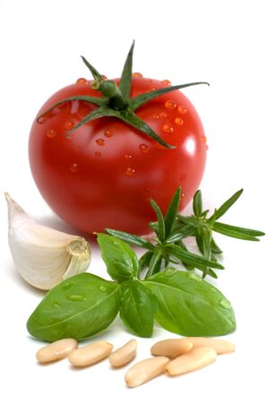 garlic cloves: Tomato with garlic cloves, rosemary, basil and pine nuts isolated against white