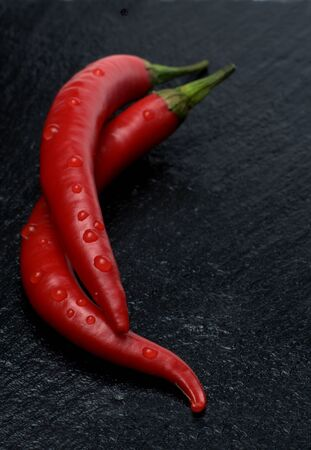 macroshot: Two red chili peppers with drops on slate tablet
