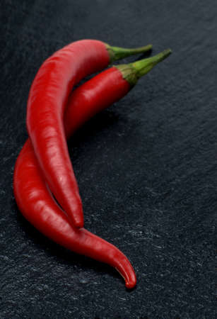 macroshot: Two red chili peppers on black slate tablet Stock Photo