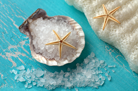 Bath salt in a mussel shell and starfishes on turquoise wood