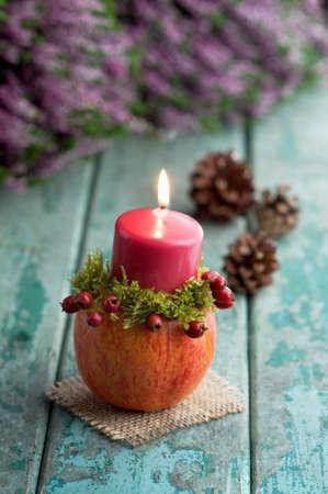 autumn motif: Autumnal decoration with candleholder on turquoise wood