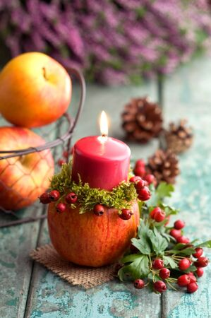 autumn motif: Autumnal decoration with candle on turquoise wood