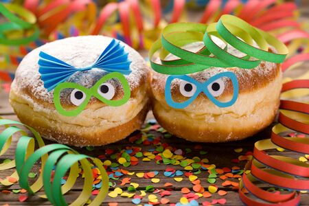 Carnival doughnuts with funny faces and paper streamers