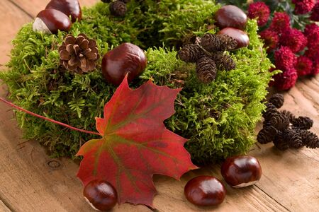 Autumnal decoration - moss wreath with chestnuts on wood Stok Fotoğraf - 87514650