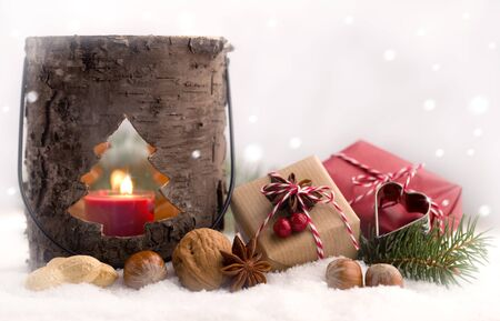 Cute Christmas presents and lantern in a snow-covered landscape
