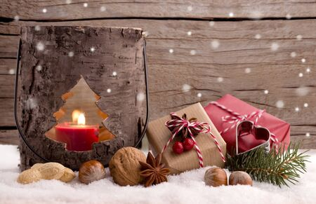 Christmas presents and lantern in the snow against a wooden fence