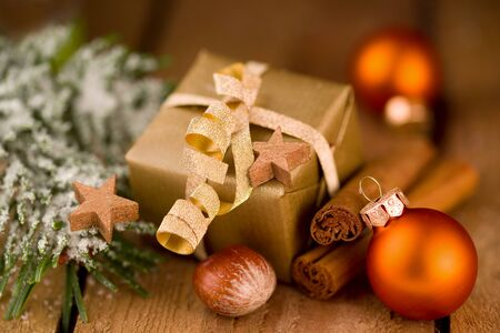 Cute golden Christmas gift with decoration on wooden boards