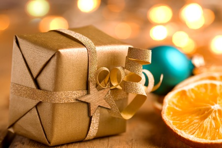 Cute golden Christmas present with lights on old wood Stock Photo