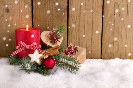 Christmas gifts and candle in the snow in front of a woodenfence Stok Fotoğraf
