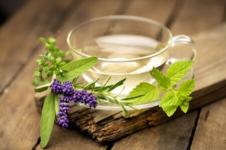 Tea glass with fresh herbs on old wood Stok Fotoğraf