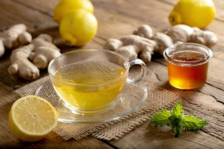 Energizing ginger tea with lemon and honey on old wooden table