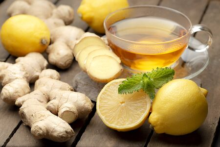 Hot ginger tea with lemon and honey on old wooden table