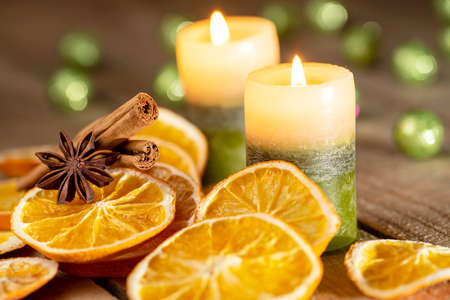 Christmas or advent decoration - orange slices, spices and candles on wooden table Stok Fotoğraf