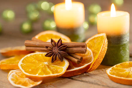 Christmas or advent decoration - candles with orange slices and spices on old wood Stok Fotoğraf