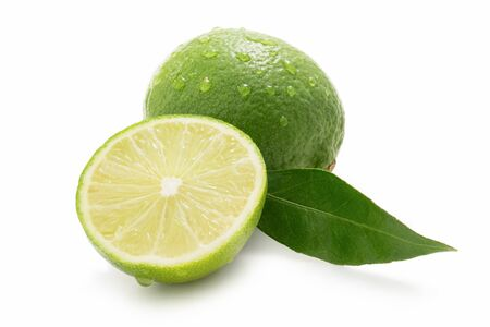 Fresh limes - one sliced - with drops of water isolated against white