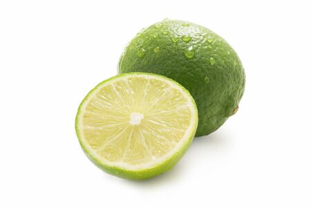Sweet limes - one sliced - with water drops isolated against white