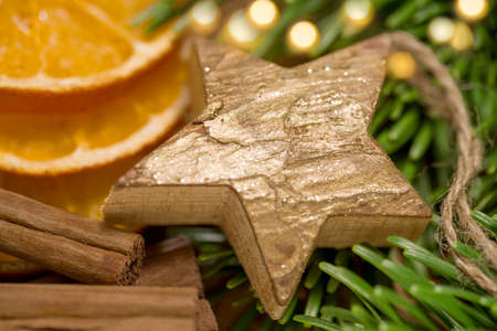 Christmas decoration - wooden star with golden colour and spices on green fir - close-up