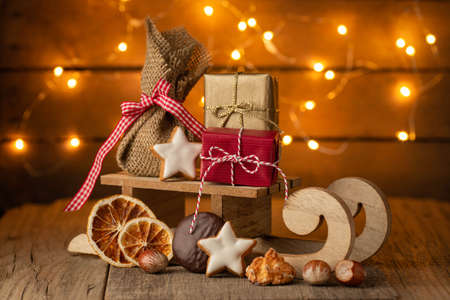 Bright Christmas - small sleigh with Christmas presents and lights on old rustic wood Stok Fotoğraf