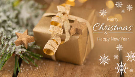 Merry Christmas - Small golden Christmas present with stars and lettering on wood Stok Fotoğraf