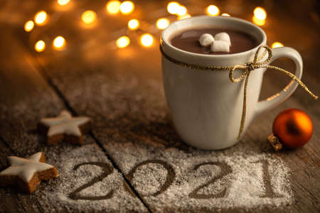 New Year's Greetings 2021 and Christmas mood - Cup of cocoa with marshmallows and lights on rustic wood