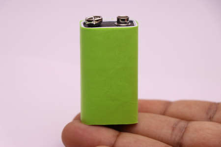 9v rechargeable battery or alkaline battery with space for copy text held in hand on white background