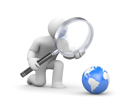 investigating: The person examines globe Stock Photo