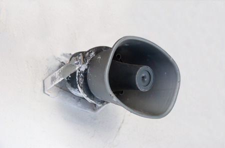Grey loudspeaker hanging on a white wall Stock Photo