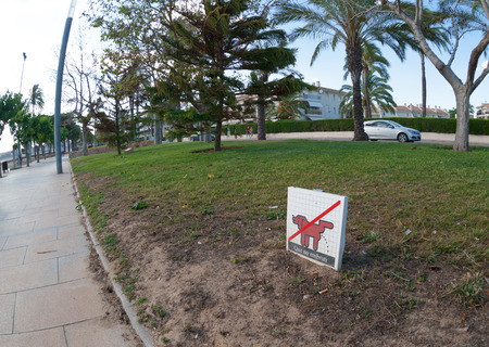 prohibits: Sign stand jn the lawn and which prohibits walking the dogs Stock Photo