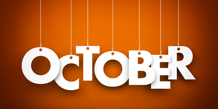 calendar october: October word suspended by ropes on brown background Stock Photo