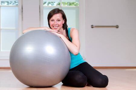 Beautiful young and athletic woman smile on a fitness ball Stock Photo - 14308657