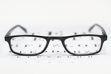 refractive: glasses on the background of eye test chart