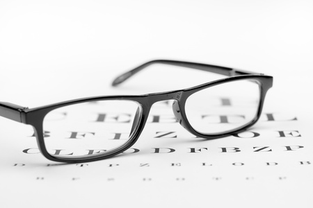 writing on glass: glasses on the background of eye test chart