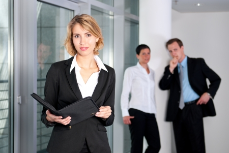 Woman with a folder before group discussed photo