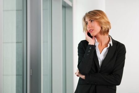 seriously: blond business woman on the phone