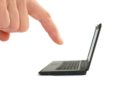 Concept - Krimpende technologie. Hand met de wijsvinger met behulp van een miniatuur laptop. Stockfoto