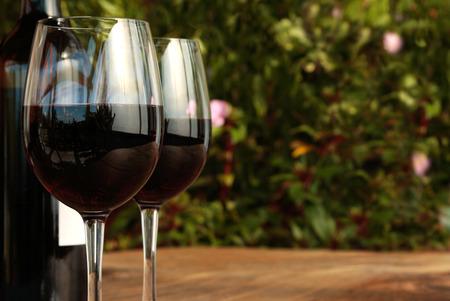 Fles en glazen rode wijn op een outdoor houten tafel