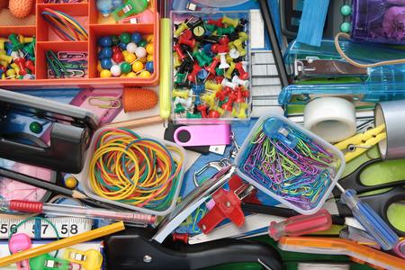 grapadora: Vista elevada de los contenidos de colores del cajón de escritorio Foto de archivo
