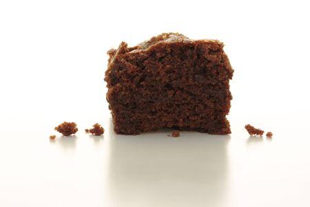 Rechtdoor oog van een stuk chocolade brownie, bovenste helft geïsoleerd op wit Stockfoto