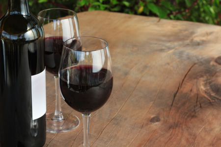Fles glazen rode wijn op een outdoor houten tafel