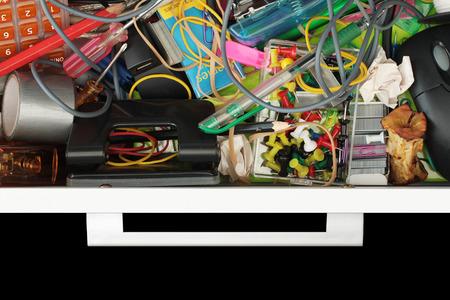 oficina desordenada: Vista elevada del mundo sórdido del cajón de escritorio desordenado aislado en negro con copia espacio Foto de archivo