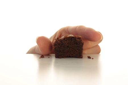 Stiekeme hand die voor het laatste stuk chocolade brownie, bovenste helft geïsoleerd op wit Stockfoto