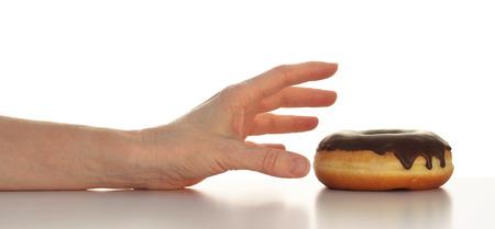Arm met de hand te bereiken voor een lekkere chocolade bedekte donut bovenste helft van de foto op wit wordt geïsoleerd Stockfoto - 42656936