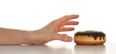white yummy: Arm with hand reaching for a yummy chocolate topped doughnut top half of photo isolated on white