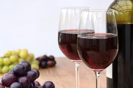 Fles glazen rode wijn op een outdoor houten tafel met druiven, lichte achtergrond Stockfoto