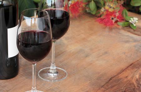 Fles en glazen rode wijn op een outdoor houten tafel met Pohutukawa bloeiende