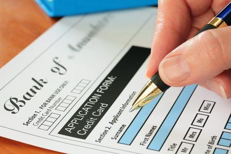 Hand met pen invullen van een credit card applicatie bank vorm zijn fictief gemaakt door fotograaf