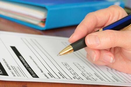 Hand met pen invullen van persoonlijke gegevens op een formulier formulier wordt fictief gemaakt door fotograaf