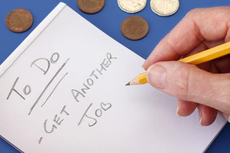 Hand met potlood maken van een notitie naar een andere baan te krijgen om te proberen om meer geld, op een paar munten in de achtergrond te verdienen Stockfoto