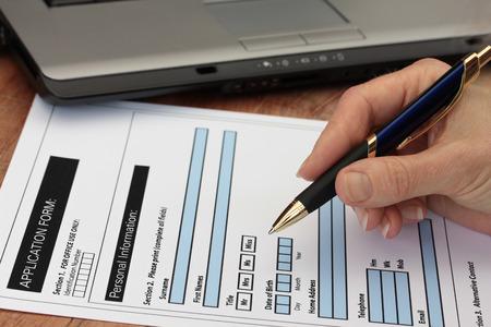 Hand met pen invullen van een formulier met een laptop op de achtergrond vorm is fictief Stockfoto